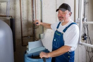 Worker installing water softener